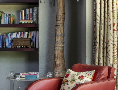 FAMILY ROOM DETAIL – Family room reading nook with glass chained standing lamp in mangrove wood. One of pair of Roche Bobois Art Deco styled armchairs in burnt red leather with Autumn linen curtaining.