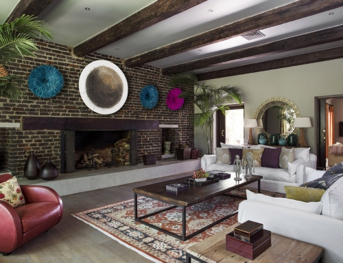 FAMILY ROOM FIREPLACE – The original fireplace was kept, the brick exposed to highlight a now colourful display of feathered hats and an eastern themed artwork by Abe Oppermann.