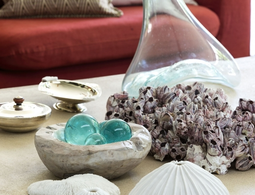 FORMAL LOUNGE COFFEE TABLE DETAIL – A cement coffee table displaying a collection of  Art Deco silver bowls, recycled blown glass and sea themed objects d'art. Effectively capturing light as a focal point.