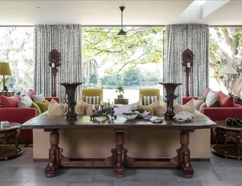 FORMAL LOUNGE ROOMSCAPE – Panoramic view from the entrance hall into the formal lounge and out the oversized vista doors. An Indian tannery table is decorated by late 19th Century Japanese bronze vases and bronzed décor.