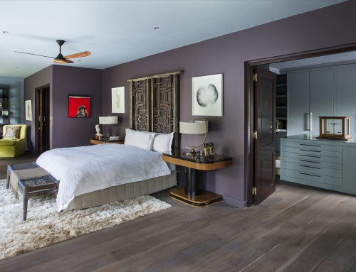 MASTER SUITE BEDROOM – A master  bedroom in tones of dusty purple  and blue. A pair of English Art Deco pedestals by Harry & Lou Epstein used as bedside tables. A pair of Indian balustrades  hung vertically off the wall form the headboard. Artworks  by  Robert Hodgins and Stefanus Rademeyer.