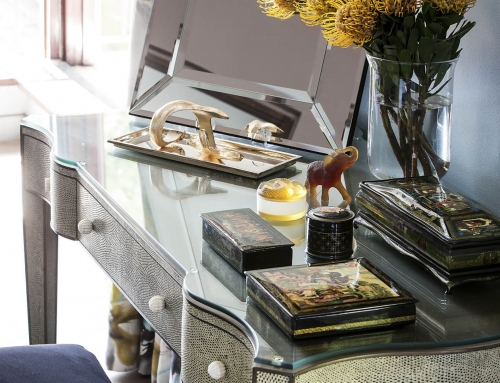 MASTER SUITE DRESSING STATION – A faux reptile skin dressing table displays a selection of Russian lacquer boxes, Lalique and Daum glass next to a Ralph Lauren tray. The linen curtains in a gauche floral, lifting the colours in the room.