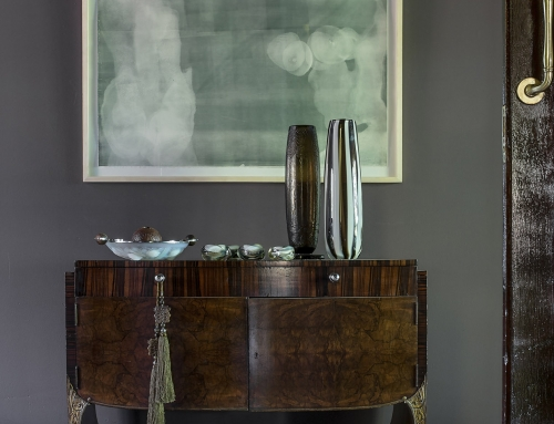 MASTER SUITE FOYER – The foyer to a master suite displays a French Art Deco console dressed with jade, cameo, opalescent, and recycled blown glass. Artwork a monotype by Jessica Webster.