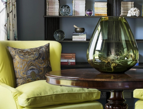 MASTER SUITE READING NOOK – A lemon rind cotton armchair offsets a Victorian mahogany barrel table.  The hand blown vessel houses an air plant. The 1930 Indian iron bookshelf displaying collectibles and Russian lacquered nesting dolls.